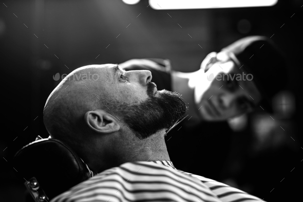 Black and white photo. Fashion barber dressed in a black clothes tidies up men's beard and - Stock Photo - Images