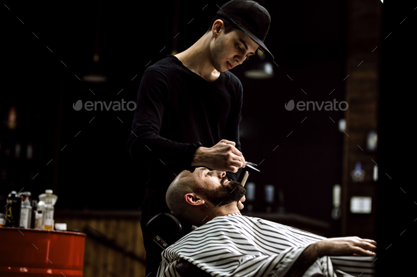 Men's style. The barber dressed in a black clothes scissors beard of brutal man in the stylish - Stock Photo - Images