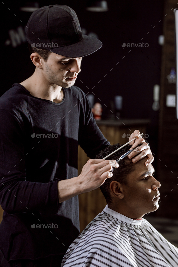 The barber dressed in black clothes is cutting a man's hair holding scissors and comb in his - Stock Photo - Images