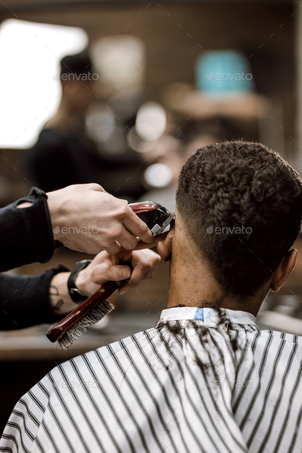 The barber makes a razor cut hair back and sides for a stylish black-haired man sitting in the - Stock Photo - Images