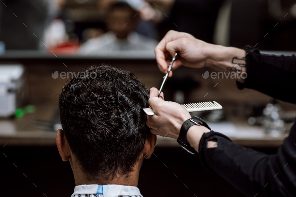 The barber is cutting a man's hair holding scissors and comb in his hands opposite the mirror in - Stock Photo - Images