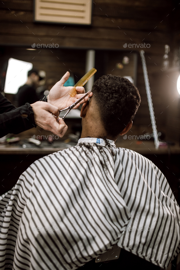 The barber scissors hair on the sides for a stylish black-haired man in the barbershop. Men's - Stock Photo - Images