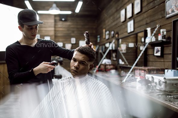 The fashion barber in black clothes makes a razor cut hair for a black-haired man sitting in the - Stock Photo - Images
