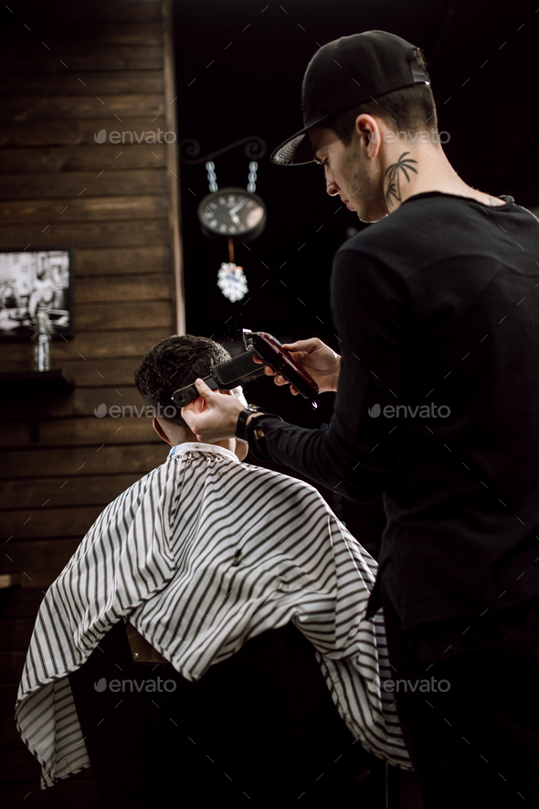 The fashion barber makes a razor cut hair for a stylish black-haired man in a stylish barbershop - Stock Photo - Images