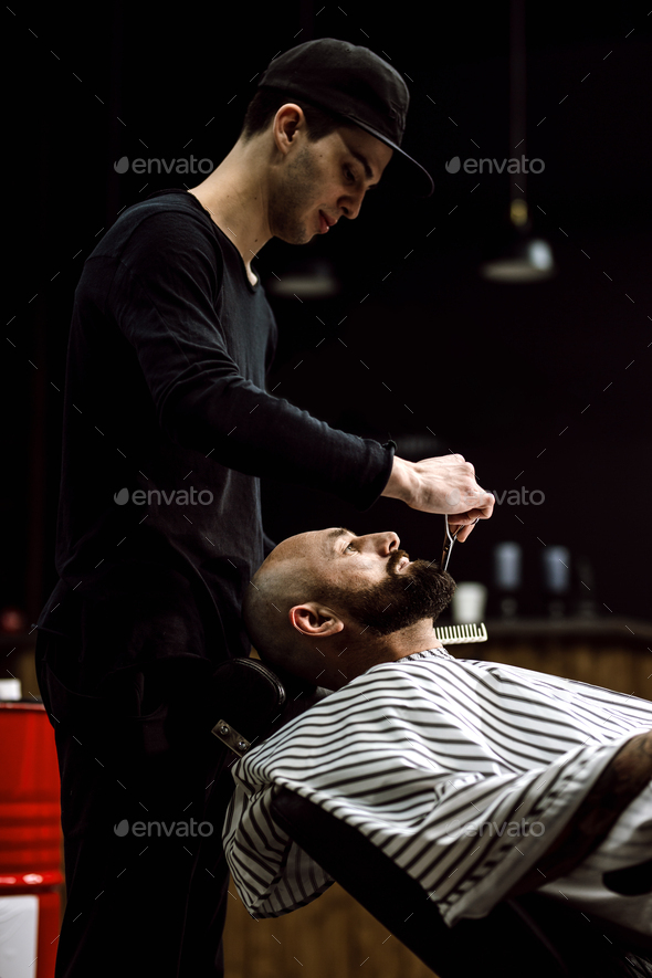 Men's fashion. The barber dressed in a black clothes scissors beard of brutal man in the stylish - Stock Photo - Images