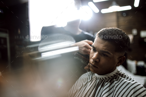 The fashion barber in black clothes makes a razor cut hair for a stylish black-haired man sitting in - Stock Photo - Images