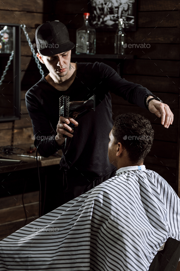 The stylish barber dressed in black clothes dries man's hair in a barbershop - Stock Photo - Images