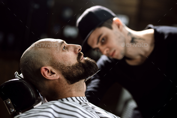 The barber dressed in a black clothes scissors beard of brutal man in the stylish barbershop - Stock Photo - Images