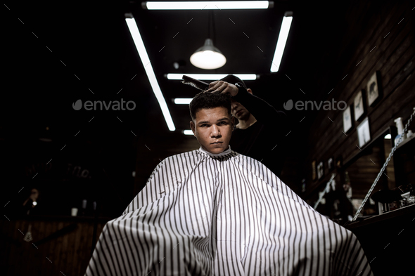 The stylish barbershop. The fashion barber makes a stylish hairstyle for a black-haired man sitting - Stock Photo - Images