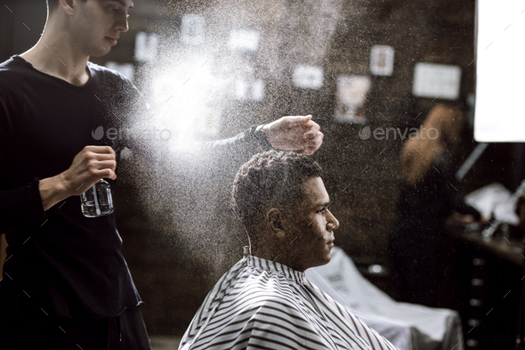 The barber dressed in a black clothes is doing the hair styling to the stylish black-haired man - Stock Photo - Images