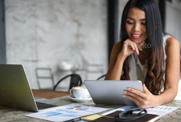 Asia female businessmen are using the tablet during leisure. She smiles happy. - Stock Photo - Images