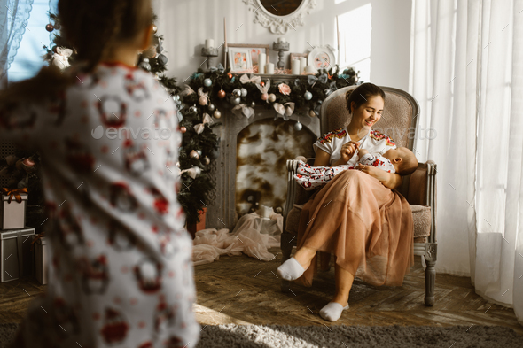 Beautiful mother sits in the armchair with her little baby next - Stock Photo - Images