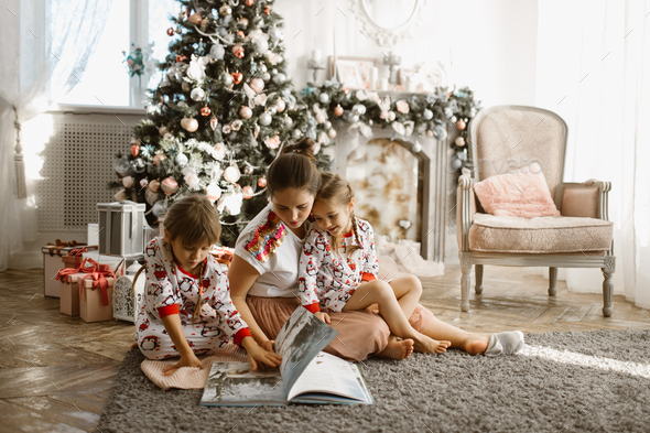 Young beautiful mother with two little daughters sit on the carpet and read book near the New Year - Stock Photo - Images
