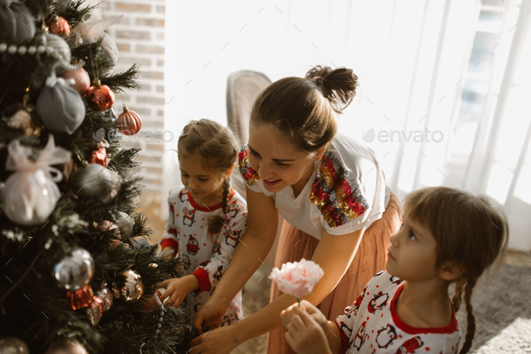Young mother with two little daughters in pajamas decorate a New Year's tree in the cozy room - Stock Photo - Images