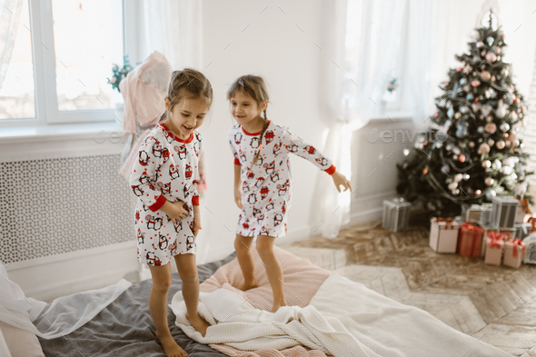 Two charming little girls in their pajamas are having fun jumping on a bed in a sunlit cozy bedroom - Stock Photo - Images