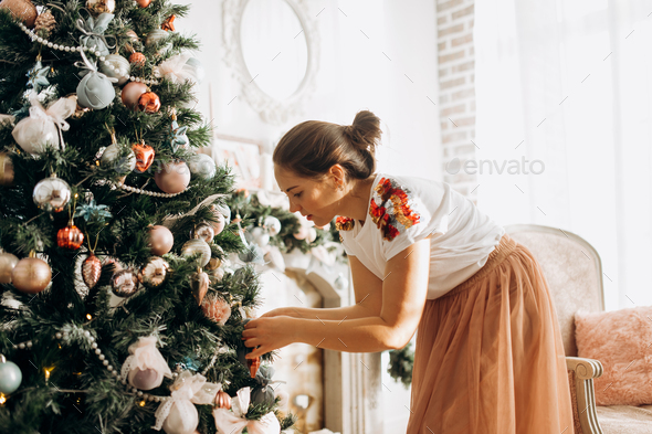 Young beautiful woman decorates a New Year's tree in the full of light cozy room - Stock Photo - Images