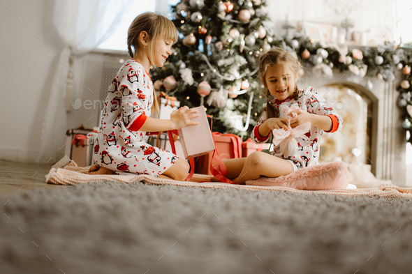 Two happy little sisters in pajamas sit on the carpet and open New Year's gifts in the light - Stock Photo - Images