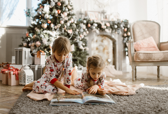 Two little sisters sit on the carpet and read book near the New Year's tree with gifts in the - Stock Photo - Images