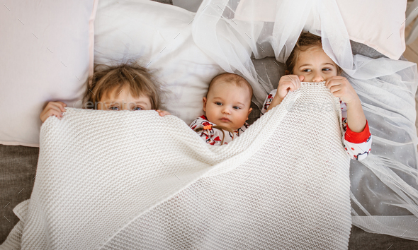 Two little sisters and a tiny brother lie on the bed under the white blanket in the light cozy - Stock Photo - Images