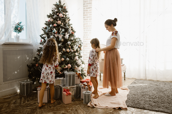 Caring mother braids her little daughter's braid while second daughter decorates a New Year' - Stock Photo - Images