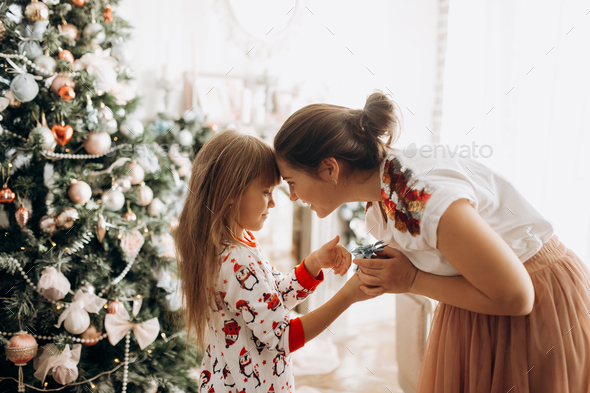 Gentle mother with her little daughter dressed in pajama next to the New Year's tree in the full - Stock Photo - Images