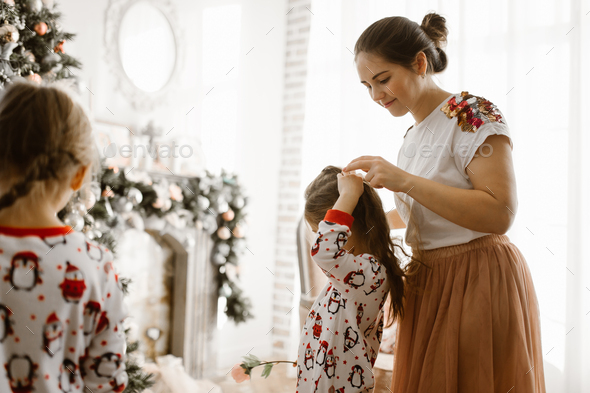Beautiful mother braids her little daughter's braid in the light cozy room with wonderful New - Stock Photo - Images