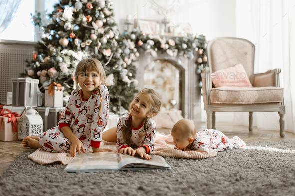 Two little sisters and a tiny brother lie on the carpet and read - Stock Photo - Images