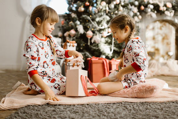 Two little sisters in pajamas sit on the carpet and open New Year's gifts in the light cozy room - Stock Photo - Images