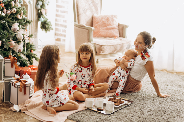 Mother with a baby on her hands sits o the carpet with her two daughters dressed in pajamas eating - Stock Photo - Images