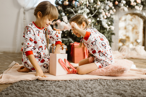 Two little sisters in pajamas sit on the carpet and open New Yea - Stock Photo - Images