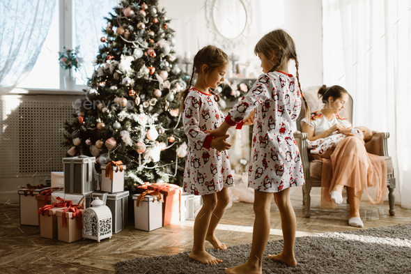 Two little sisters in pajamas having fun New Year's tree with gi - Stock Photo - Images