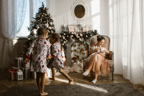 Two little sisters in pajamas having fun New Year's tree with gifts in the light cozy room and - Stock Photo - Images