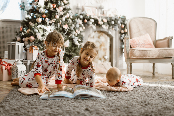 Two little sisters and a tiny brother lie on the carpet and read book near the New Year's tree - Stock Photo - Images
