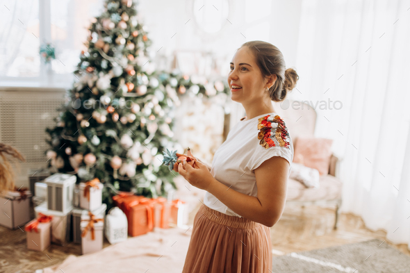 Young beautiful mother holds New Year's decorations standing in the full of light cozy room next - Stock Photo - Images