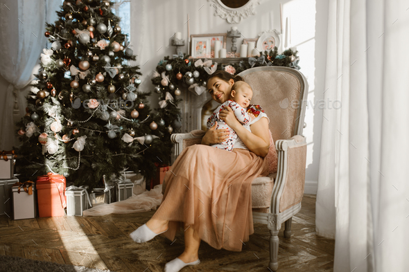 Beautiful mother sits in the armchair with her little baby next to the fireplace and New Year's - Stock Photo - Images