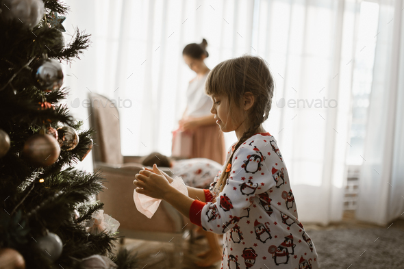 One little girl in pajama decorates a New Year's tree in the light cozy room - Stock Photo - Images