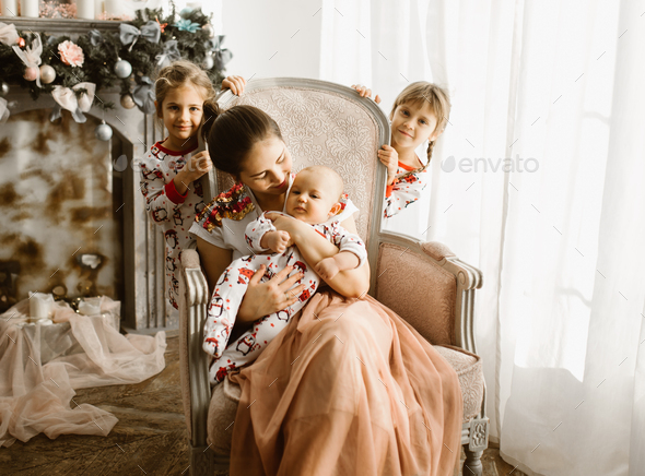 Beautiful mother sits with her little baby in the armchair next to the fireplace in the light cozy - Stock Photo - Images