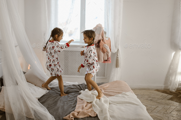 Two little girls in their pajamas are having fun jumping on a bed in a sunlit cozy bedroom - Stock Photo - Images
