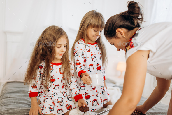 Young mother is bringing cocoa with Marshmallows and cookies to her daughters in pajamas sitting on - Stock Photo - Images
