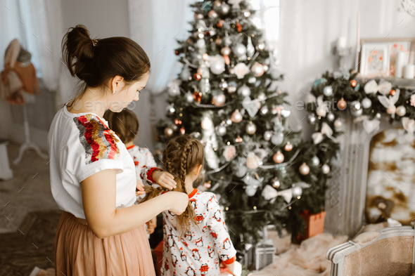 ?aring mother braids her little daughter's braid while second daughter decorates a New Year' - Stock Photo - Images