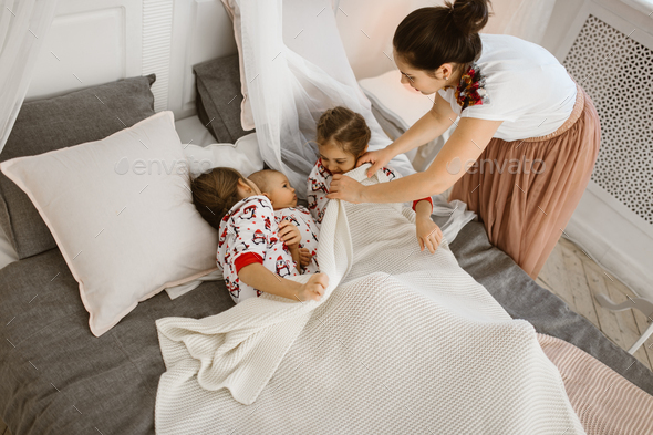 Young mother covers a white blanket for two daughters and a tiny son who lie on the bed in a light - Stock Photo - Images