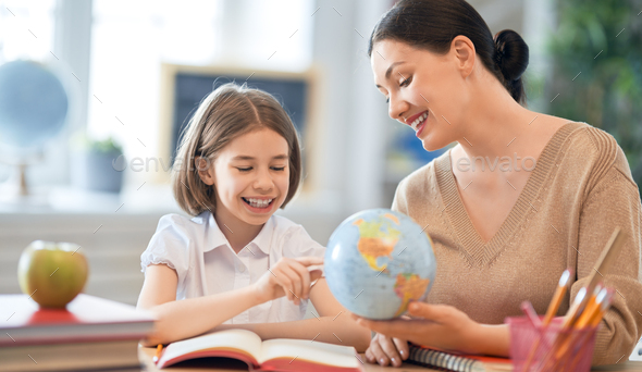 Girl with teacher in classroom. - Stock Photo - Images