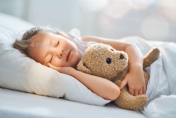 child is sleeping in the bed - Stock Photo - Images