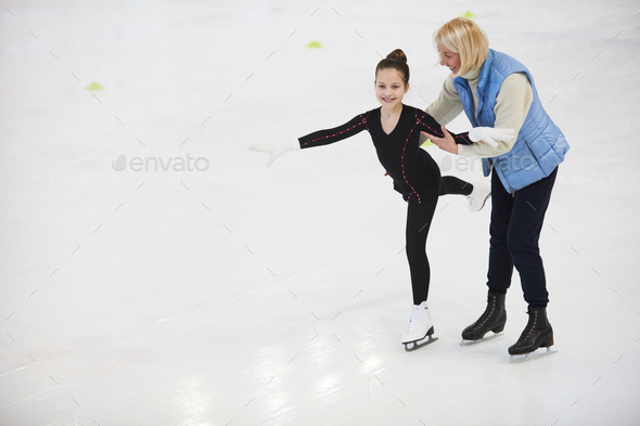 Coach Helping Girl Figure Skating - Stock Photo - Images
