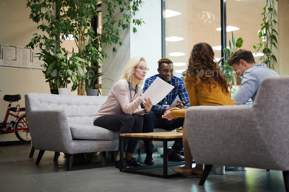Lady reading report to colleagues at meeting - Stock Photo - Images