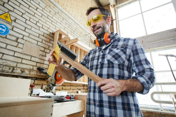 Cheerful carpenter using triangle ruler - Stock Photo - Images