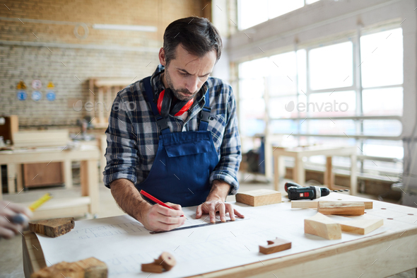 Thoughtful carpenter making sketch - Stock Photo - Images