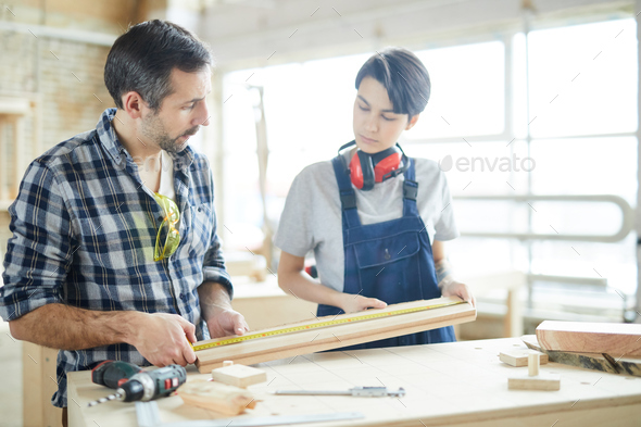 Carpenters checking measurement of wooden plank - Stock Photo - Images