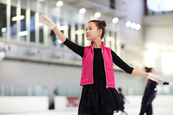 Asian Girl Figure Skating in Rink - Stock Photo - Images