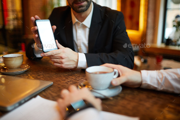 Businesman Presenting Smartphone - Stock Photo - Images
